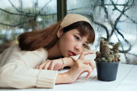 Brunette girl in beige headband bend down on the table and touch the mini cactus in rainy day while she miss her beloved one.
