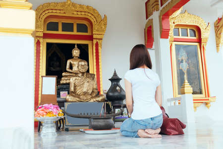 Long hair woman in casual look sitting in front of Buddha statue and pray.