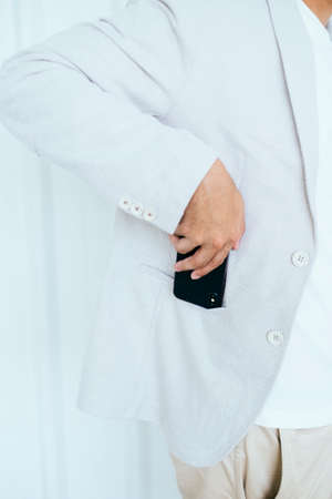 Cropped image of man's hand pick a smartphone out of pocket.