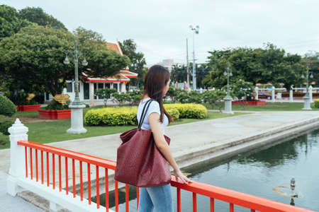 Long hair woman in white t-shirt and jeans standing on the red bridge looking at the fish in the river. 版權商用圖片