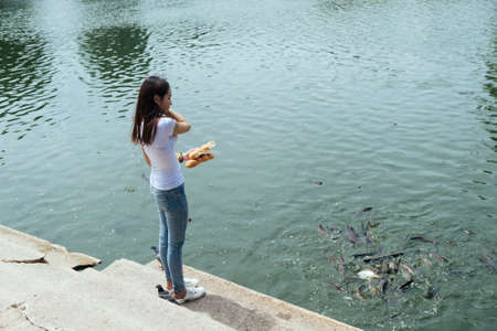 Casual look woman feeding the fish in the lake with bread.