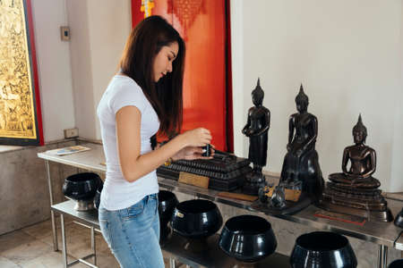 Long hair woman in casual look preparin the coin to drop into the monk's alms-bowl in front of the Buddha statue.