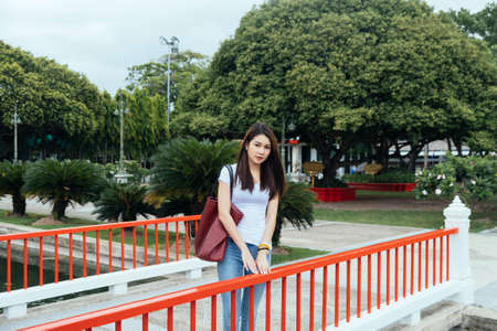 Long shot of casual woman in white t-shirt and jeans standing on the bridge with the garden as a background.
