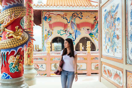 Long hair woman in casual look walking on the terrace of the temple along the wall with painting angel.