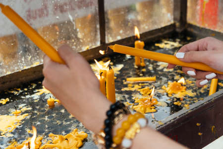 Cropped image of woman's hands try to light the candle for praying in the temple.
