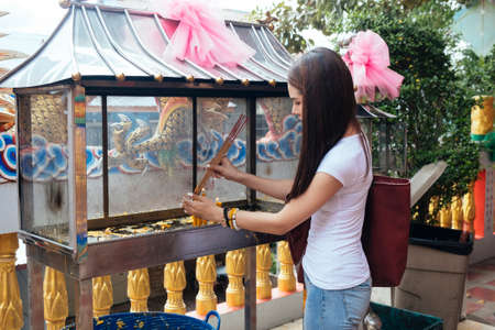 Long hair woman in casual clothes try to burn joss stick with the candle.