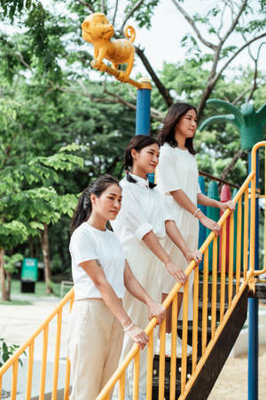 Triple twin sister standing on the stair of toy in playground and grab the handrail. Stockfoto