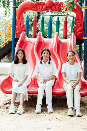 Triple twin sister sitting at the end of red slider together.