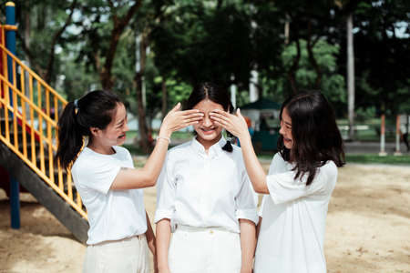 Triple twin sister stand at the playground in the park, two of them close the eyes of pigtails girl.
