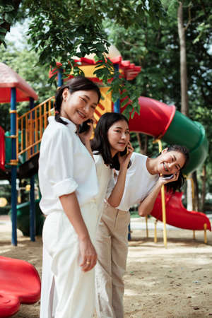 Triple twin sister answer the phone call while standing at the end of red slider in the playground of the park.