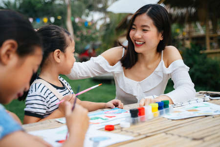 Cheerful asian big sister touching her little sister head as compliment. Two sister paining water colour on paper at outdoor park.