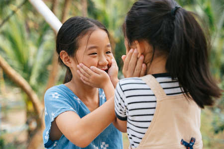 Playful little asian girl touching face to face in nature. Sisters enjoy playing together at farm. Traveling in nature. Countryside area.