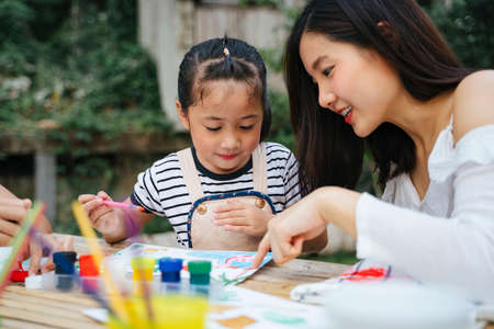 Asian big sister helping little sister painting water colour on paper outdoors. Imagens