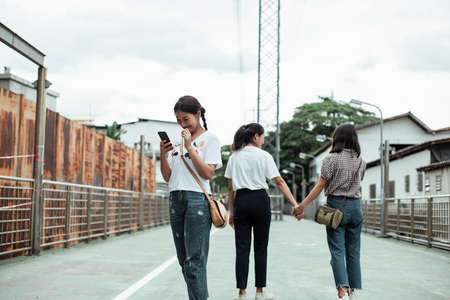 Triple twin in the old town, two of them hold each other hands and walking together while left another one use her smartphone. Stockfoto
