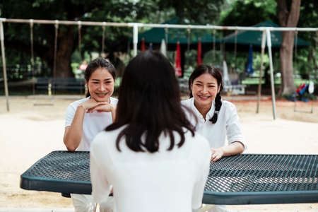 Triple twin sister sitting together at the metal table in the park next to the playground. Stockfoto
