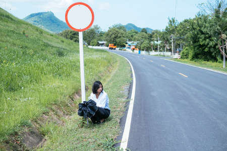 Young asian woman sitting on the side of the road with black umbrella, close to empty sign pole.