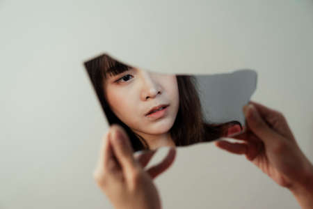 The broken mirror reflect the face of introspective Thai girl due to she lost the meaning of her life.