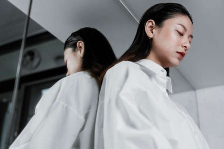 Low angle shot of black long hair woman leaning against the mirror and close the eyes.