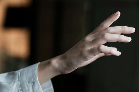 Cropped image of woman's hand reach out to grab something in the air. Stock Photo