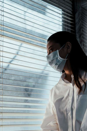 Long hair woman wear the hygienic mask at the window.
