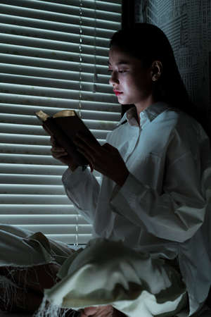 Woman in white clothes sit at the window and read the book with no light. Stock Photo