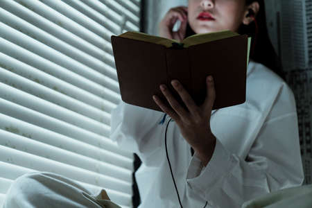 Cropped image of a book in woman's hand while she read it at the window.