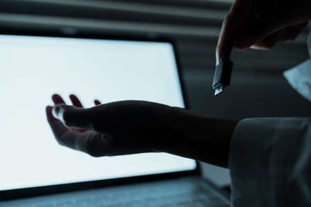 Cropped image of woman's hand while she connect herself to the laptop via USB cable.