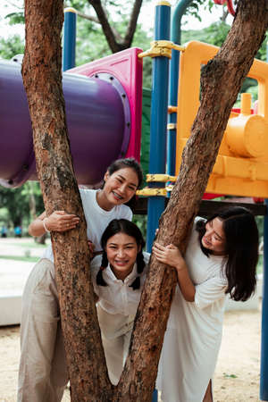 Triple twin sister play together around the tree like V sign with happiness in the playground. Stockfoto