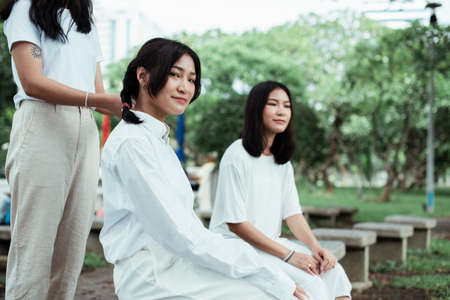 Triple twin sister are in the park, one of them make a pigtails hair for another one.