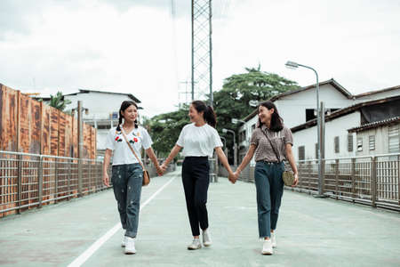 Triple twin sister holding each other hands while walking in the old town at the street.