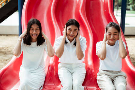 Triple twin sister sitting at the end of red slider inthe playground, close their ears. Stockfoto