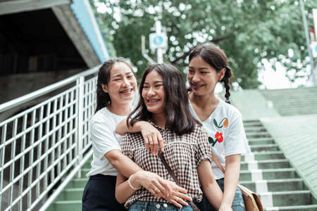 Triple twin sister standing and hug each other on the stair. Stockfoto