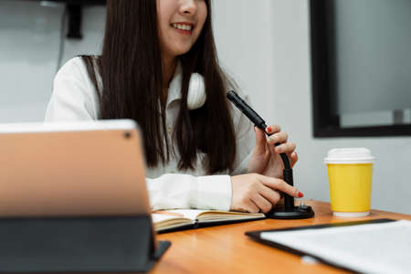 Cropped image of black long hair girl in white shirt with white headphone around neck while check the microphone. Stock Photo