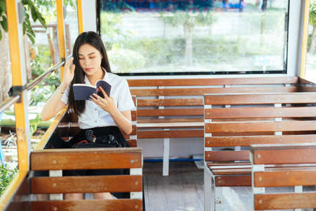 Black long hair college girl in uniform sitting on the empty bus reading the book. Stock Photo
