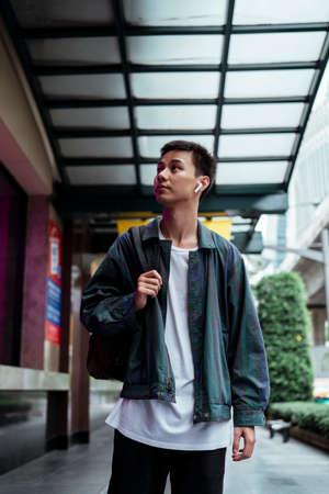 Short hair guy in jacket wearing bluetooth earphone walking in the city and looking around. Standard-Bild