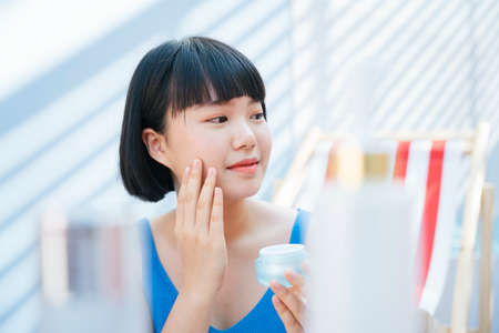 Beautiful bob haircut asian woman in blue tank top shirt holding cream lotion bottle jar on hand, applying cream on face in the room.