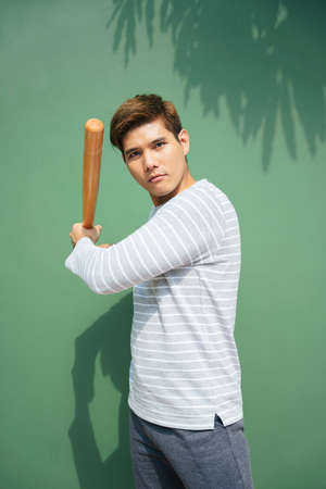 Young handsome asian man hold wooden baseball bat over green background. Baseball player on vacation.