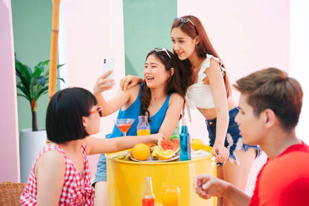 Women taking selfie with smartphone in summer party. Group of people enjoy party.