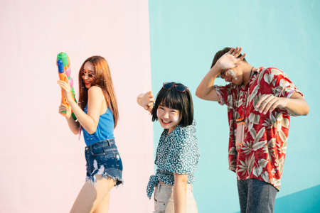 Songkran festival concept. Three people enjoy water festival in Songkran day. Isolated on pastel pink blue background. Portrait of three young thai people having fun in Songkran festival in Bangkok, Thailand.