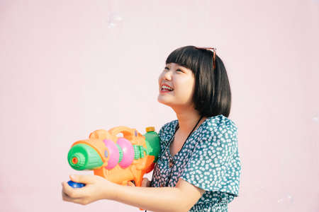 Beautiful short bob hairstyle woman enjoy Songkran water festival in Thailand with water gun. Cheerful and happiness. Modern songkran. Isolated on pink background. Songkran in Bangkok.