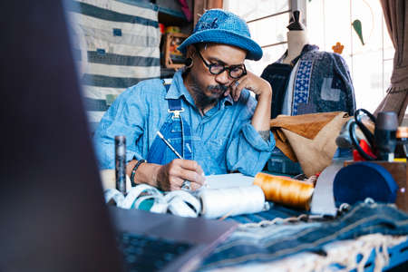 A man in blue clothes, hat and apron draw the pattern of his clothes on the paper with pencil and call someone by smartphone.