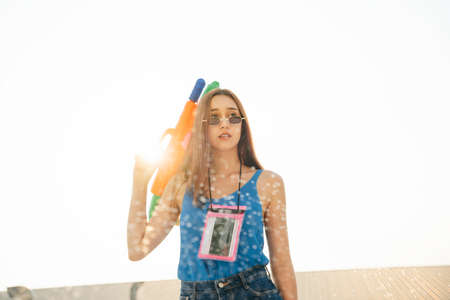 Beautiful sexy woman wearing blue tank top vest shirt and sunglasses holding water gun. Songkran festival concept. Sunset time.
