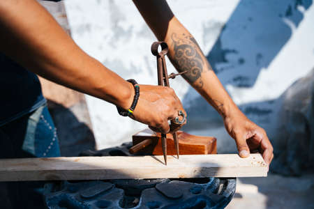 Craftmans measure the plank and use the shaving to make it thin, dividers on the plank. 免版税图像