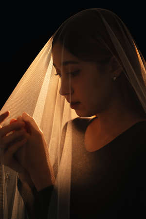 Beautiful mixed race woman seal inside the bride viel. Wife ghost. Isolation over black background.