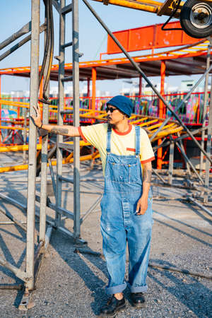 A man in yellow t-shirt and denim overalls standing in the abandoned amusement park in sunny day.