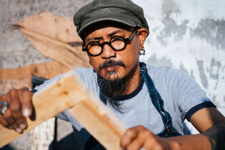 The carpenter man make the frame from wooden by himself, right angle, perpendicular. 免版税图像
