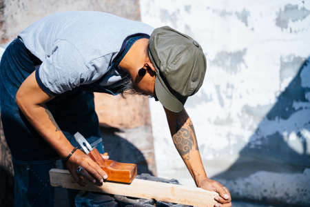 Craftmans measure the plank and use the shaving to make it thin.