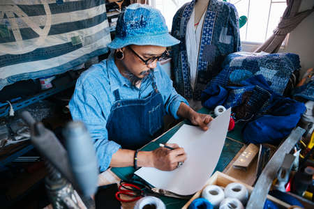 A man in blue clothes, hat and apron draw the pattern of his clothes on the paper with pencil and look at the reference on the internet by smartphone.