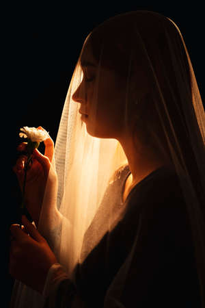 Beautiful mixed race woman holding white flower seal inside the bride viel. Wife ghost. Isolation over black background.