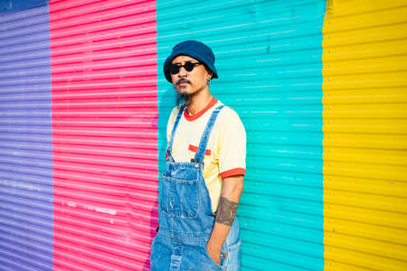 The man in yellow t-shirt and denim overalls standing and sitting in front of colorful shutter door in sunlight.
